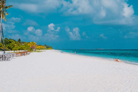 Maldives with turquoise clear water and many palm trees and clouds in the sky