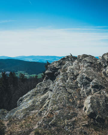 View from the top of a mountain into the valley with clouds in the blue sky and beautiful green trees and lots of rocks