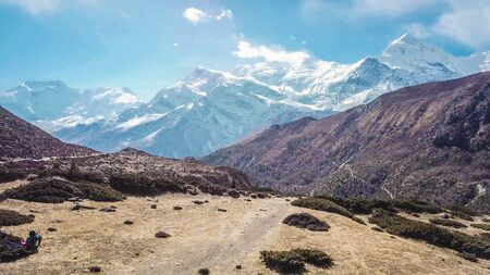 A mountain chain in the Himalayas that is covered with snow. This is a hiking trail of the Annapurna circuit