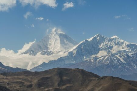 A brown hill and in the background sharp, snowy and high mountain peaks in the Himalayas in Nepal.