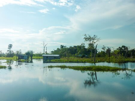 A small village of one family in the Amazon rain forest in Brazil. During flood season the houses appear to be build on the water. However during dry season you see that the houses are build on stalks.