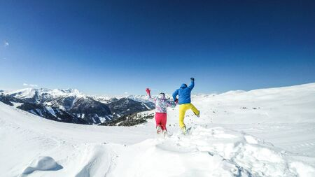 Austria is famous for its ski slopes. During winter this country turns into a winter wonderland full of joy and happiness. A couple jumping into the snow out of happiness.