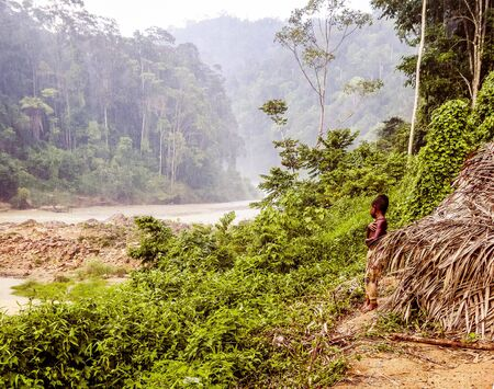 The Taman Negara Pahang in Malaysia is one of the worlds oldest deciduous rainforest. This native boy went out of his house after a heavy rainfall. The boy is observing the river. Фото со стока
