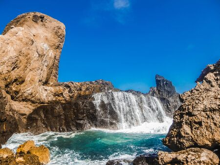 When the sea gets rough the waves are breaching the rocks splashing over their surface and creating a temporary waterfall. This phenomena is on the island of Lombok(next to Bali) in Indonesia. Stockfoto