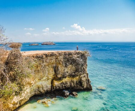 A girl standing on a dramatic cliff at the Pink Beach on the island of Lombok in Indonesia (next to Bali).