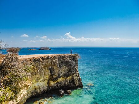 A boy standing on a dramatic cliff at the Pink Beach on the island of Lombok in Indonesia (next to Bali).