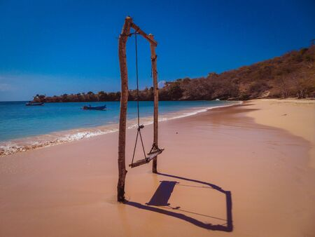 A swing on an isolated beach called the Pink Beach on the island of Lombok (next to Bali) in Indonesia. Pink and red colored corals are generating this colors. Archivio Fotografico - 130135903