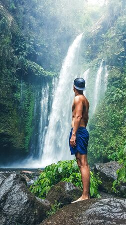 Beautiful Waterfall in Lombok, Indonesia - Sendang Gile. Man standing on the slippery stones on the side of the waterfall. Feeling of Freedom and Power Фото со стока