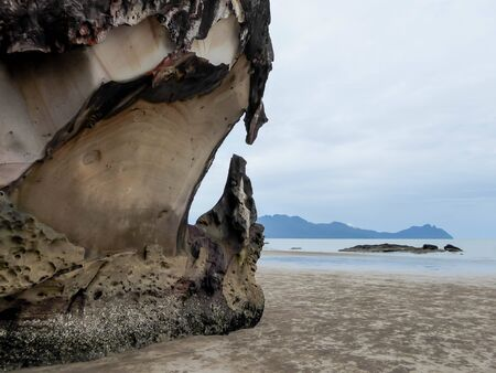 Dangerously looking,  sharp rock formation on the beach in Borneo, Bako National Park of Malaysia. Soft colors, islands visible in the background.