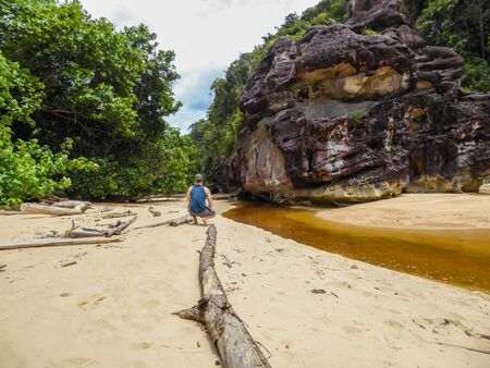 Yellow colored river getting into the sea in Borneo, Malaysia. Yellowish and brownish rock formations and the forest on the sandy shores of the river. Man squationg on the shore of the river.
