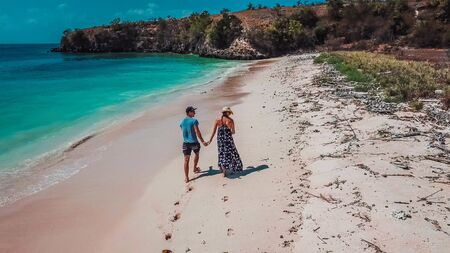 A couple walking on the Pink Beach in Lombok, holding hands. This place is a hidden gem, not spoiled by tourists. Solitude and calm feelings, waves gently spreading on the beach. Banco de Imagens