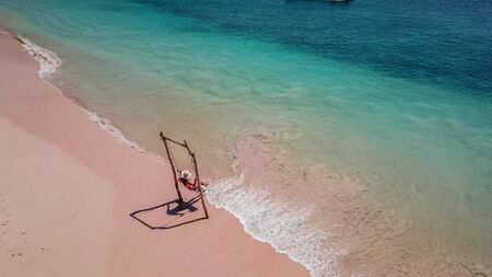 A girl swinging on the beach swing on Pink Beach, Lombok, Indonesia. Captured from above with a drone. The water changes colors from turquoise to navy blue. beach has a nice coral color.