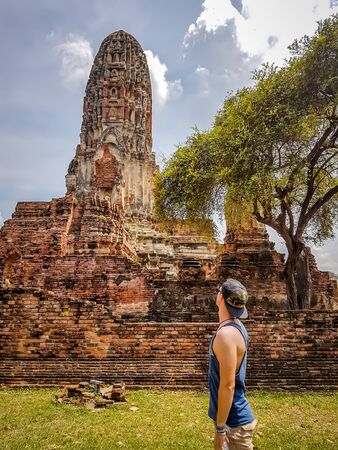 A boy admiring buildings in Ayutthaya Historical Park, Thailand. UNESCO list. Ruins of an ancient city, built of bricks. beautiful and clear day.  Green contrasted with orange and blue Reklamní fotografie
