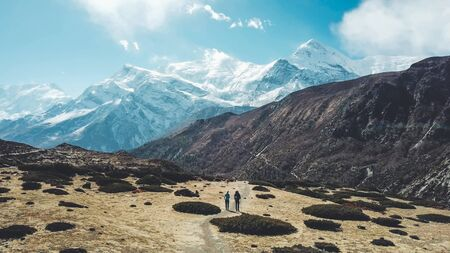 A couple trekking in the Manang Valley, Annapurna Circus Trek, Himalayas, Nepal, with the view on Annapurna Chain and Gangapurna. Dry and desolated landscape.  High mountain peaks, covered with snow. Фото со стока
