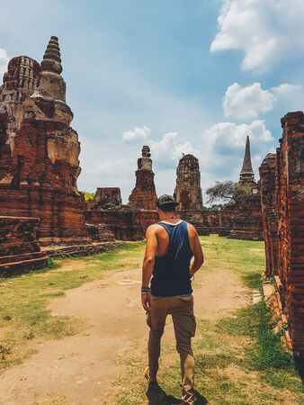 A a young man walking around Ayutthaya Historical Park, Thailand. UNESCO list. Ruins of an ancient city, built of bricks. beautiful and clear day.  Green contrasted with orange and blue. Reklamní fotografie