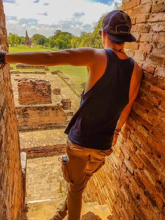 A a young man standing on one of the buildings of Ayutthaya Historical Park, Thailand, leaning on the side. UNESCO list. Ruins of an ancient city, built of bricks. beautiful and clear day.