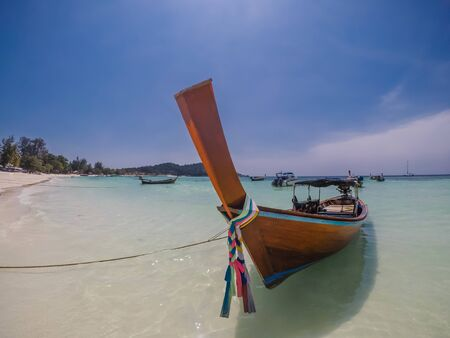 A beautifully painted boat parked on the beach on Koh Lipe, Thailand. Traditional boat type. The water in the lagoon is crystal clear. Some people walking on the beach in the back. Peaceful place. 写真素材
