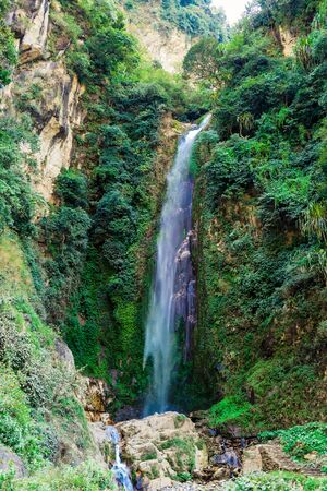 A waterfall spotted on the way to Tal, Annapurna Circuit Trek, Nepal. Few hundred meters of free fall, waterfall surrounded by tall mountains slopes, covered with green bushes and trees.
