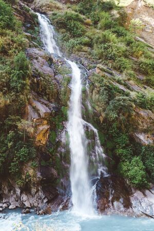 A waterfall spotted in Tal, Annapurna Circuit Trek, Nepal. Few hundred meters of free fall, waterfall surrounded by tall mountains slopes, covered with green bushes and trees. Smooth capture