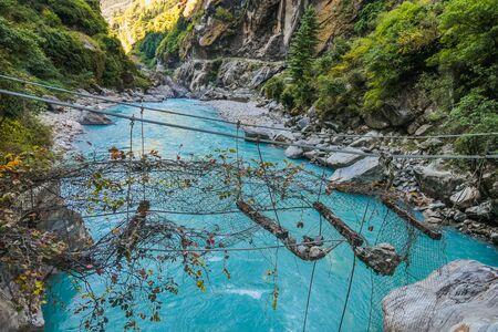 Well-worn suspension bridge, Annapurna Circuit Trek, Nepal. Not possible to cross that bridge, stones lye on it, net is broken. River flows in the gorge below the bridge. Clear day. Thriller, danger
