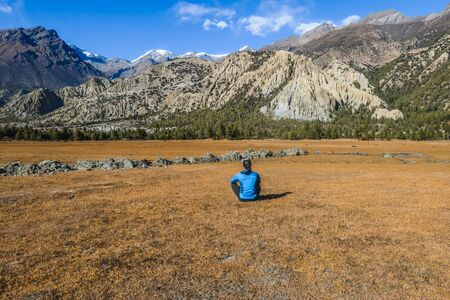 Young man sitting on the meadow in front of Himalayan Mountain Range in Humde, Annapurna Circuit Trek, Nepal. Clear sky above the peaks. Dry grass, some trees on the mountain slopes. Endless range. 스톡 콘텐츠