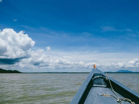 A boat tour in Bako National Park, Malaysian Borneo. Front of the boat visible to the right. Muddy color of the sea. Mountains visible in the back. Navy sky, with large amounts of the clouds.