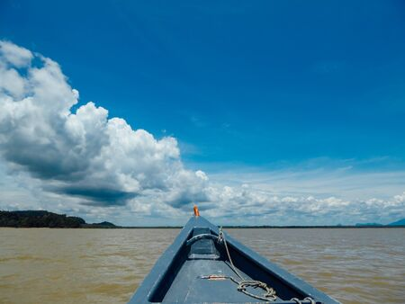 A boat tour in Bako National Park, Malaysian Borneo. Front of the boat visible in the middle. Muddy color of the sea. Mountains visible in the back. Navy sky, with large amounts of the clouds.