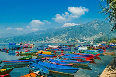 Many colourful boats parked on the shore of Phewa lake, Pokhara, Nepal. In the back Himalayan mountain range. Small villages visible on the shore. Peaceful and chilled atmosphere. Place to relax.