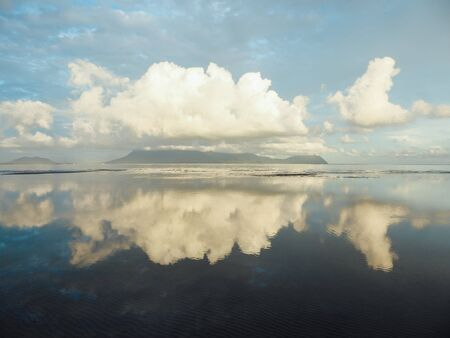 Beautiful formation of clouds over the sea in Bako National Park, Borneo, Malaysia during the sunset. Blue and yellow sky. Amazing reflection in the sea. Mountains covered with clouds in the back.
