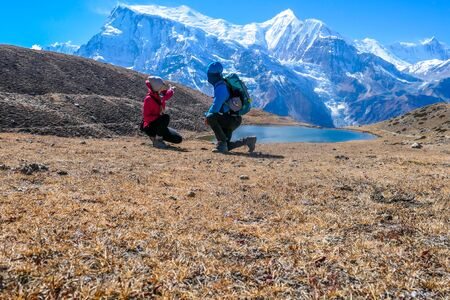 Couple squatting next to Ice lake admiring the view, Annapurna Circuit Trek detour, Himalayas, Nepal.  Annapurna chain in the back, covered with snow.  Dry grass, snowy peaks. Freedom and meditation