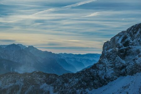 Cloudy and misty morning in Alps, Nassfeld, Austria. Delicate snow fall. Mountain slopes covered with snow. Sharp edges of the Alps. Softly colored sky. a new day begins.