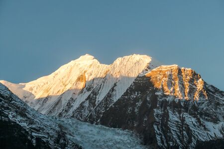 Annapurna III captured with the first sun rays on it's peak, during the sunrise. Seen from Chame, Annapurna Circuit Trek, Nepal. Clear sky above the peak. Valley still covered with shadows.