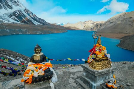 Due statue di Buddha presso il lago Tilicho, ricoperte di bandiere di preghiera. Superficie blu e calma del lago, montagne coperte dall'ombra, luce del sole nella parte posteriore. Circuito dell'Annapurna, Nepal.