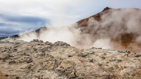 A smoke coming out of a crater in the mountains. The smoke is thick and dense. The mountains are covered with clay and mud. Orangish color of the slopes. The weather looks as it will start to rain. Banco de Imagens