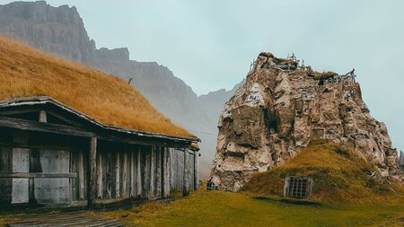 An abandoned vikings village. Roof of the cottage is overgrown with turf, a sod roof. Cottage located next to the high rock with an entrance at the bottom. In the back mountains wreathed with mist Stock fotó