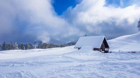 Un cottage in legno vicino alle piste da sci di Heiligenblut, in Austria. Cottage coperto di neve. Pista da sci perfettamente preparata. Alcuni alberi di pino. Cielo blu. Winder paese delle meraviglie. Sci fuoristrada. Archivio Fotografico