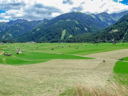 Spring came to the Alpine valley, turning the meadow into lush green color. Lots of small cottages and agricultural machinery on the grassland. High Alpine peeks around the valley. Small church. Archivio Fotografico