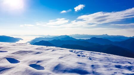 Winter mountain landscape with shoes prints in the powder snow. Bright sun makes the particles of the snow shine bright. The bottom of the valley filled with mist. Endless chains of mountains. Imagens