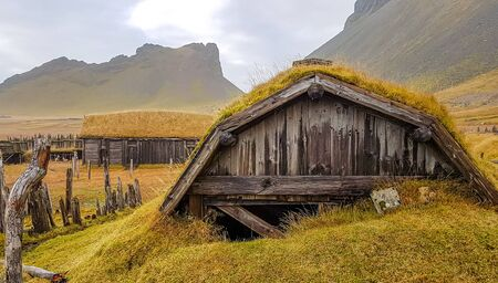 An abandoned vikings village. Sod rooftops, turf rooftops. Village located at the bottom of a high mountain. Around the farm a wooden fence. Dry grass all around. Traditional Scandinavian architecture Stock fotó