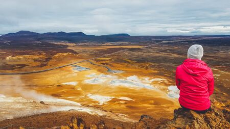Girl wearing a pink jacket sits on a top of a mud mountain, overlooking a geothermal spot noted for its bubbling pools of mud & steaming fumaroles emitting sulfuric gas. Extreme landscape.