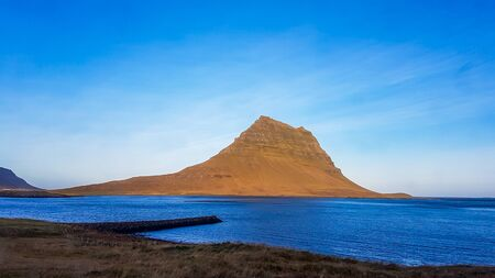 A stunning view on famous Icelands mountain, Kirkjufell. In front of the tall hat-like mountain spreads the shallow water of a fjord. Beautiful and clear day, popular destination for a holiday.