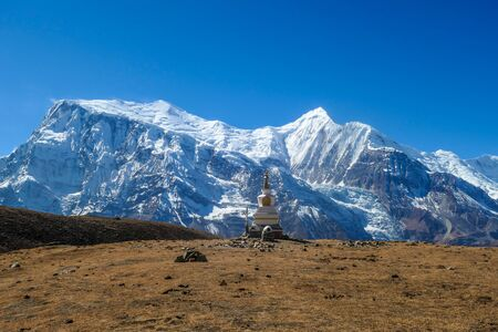 A stupa with Annapurna Chain as a backdrop, Annapurna Circuit Trek, Himalayas, Nepal. High mountains covered with snow. Land in front of the stupa is barren and dry. Some prayers flag next to it.