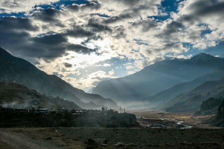 A bright day begging high in the Himalayan Mountains. Sunbeams struggle through a thick layer of clouds. Manang valley slowly wakes up to life. Serene and natural landscape. Sun brings the light.