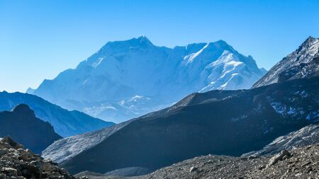 Misty Himalayan mountains, Annapurna Circuit Trek, Nepal. Sharp peaks striking out of the fog. Blue sky with overcast. Early morning, waking up to natural wonder. Complete surrender. Stock Photo