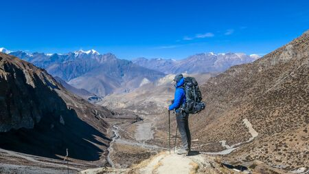 Man admires Himalayas, carries big backpack, supports himself with sticks, Annapurna Circuit Trek, Nepal. Upper Shreekharka. Dry grass. Socks dry on the backpack. Clouds in the mountains.