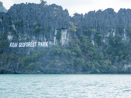 The Kilim Geoforset Park sign, seen from a boat. The sigh is situated on a mountain, rocky surface. Calm water washes the mountains. Overcast. Some smaller bushed growing on a steep rock. 版權商用圖片