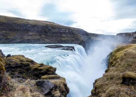 A mighty waterfall, falling into a gorge, spreading on a vast distance. Bottom of the waterfall is not visible. Gullfoss waterfall located in the canyon of the Hvítá river in southwest Iceland