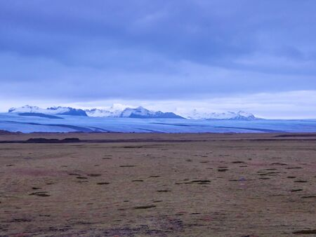 A barren grassland with the glacier's cap as a background. Thick and dark clouds are coming closer. Glacier covered in the shadow.