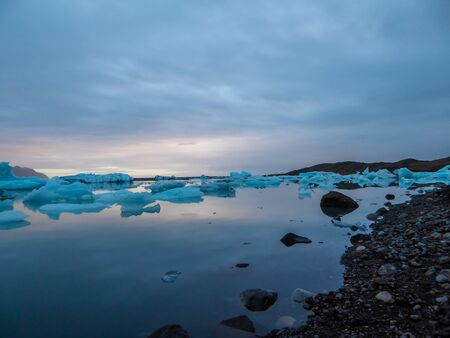 Beautiful glacier lagoon, with pebbly shore. Thousands of icebergs drifting lazily towards the sea, shining in many shades of blue. Soft sunset in the back. Thick clouds above the lagoon.