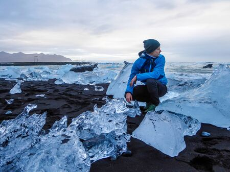 A man wearing blue jacket and a beanie squatting in between ice bergs on a diamond beach, black sand beach. Rough sea throws more ice bergs on the shore. Man is looking at the sea. Calmness